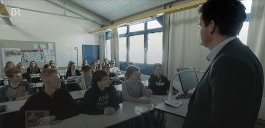 Ein junger Mann steht vor einer Klasse